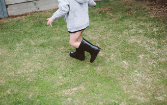 boy running on grass in black gumboots