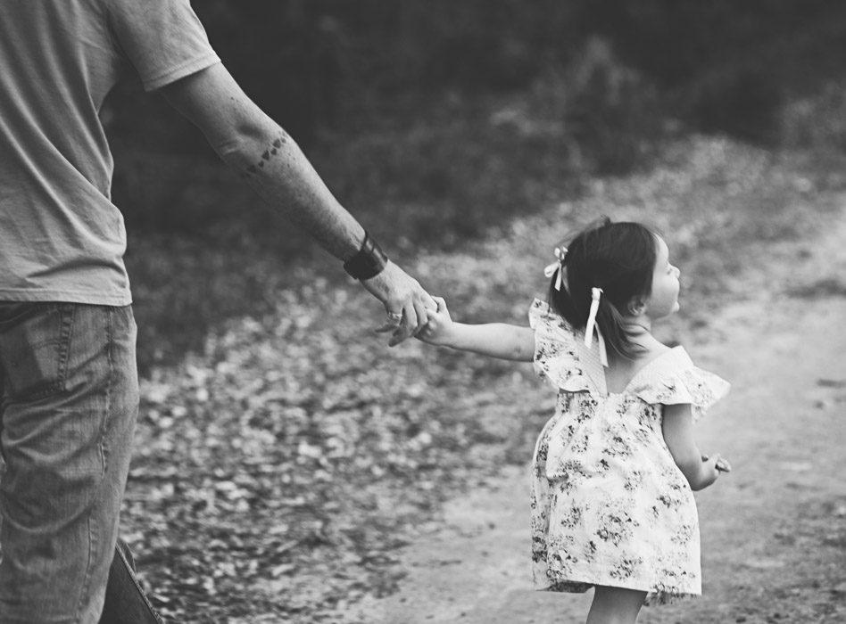 toddler holds dads hand