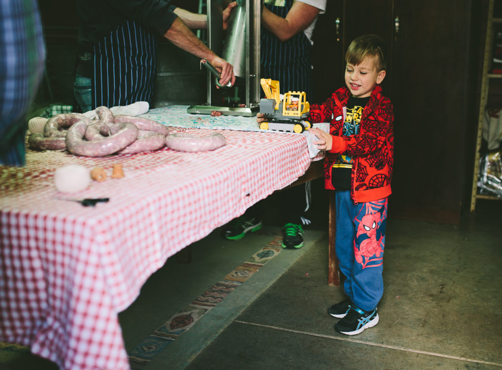 boy plays with toys on sausage making table