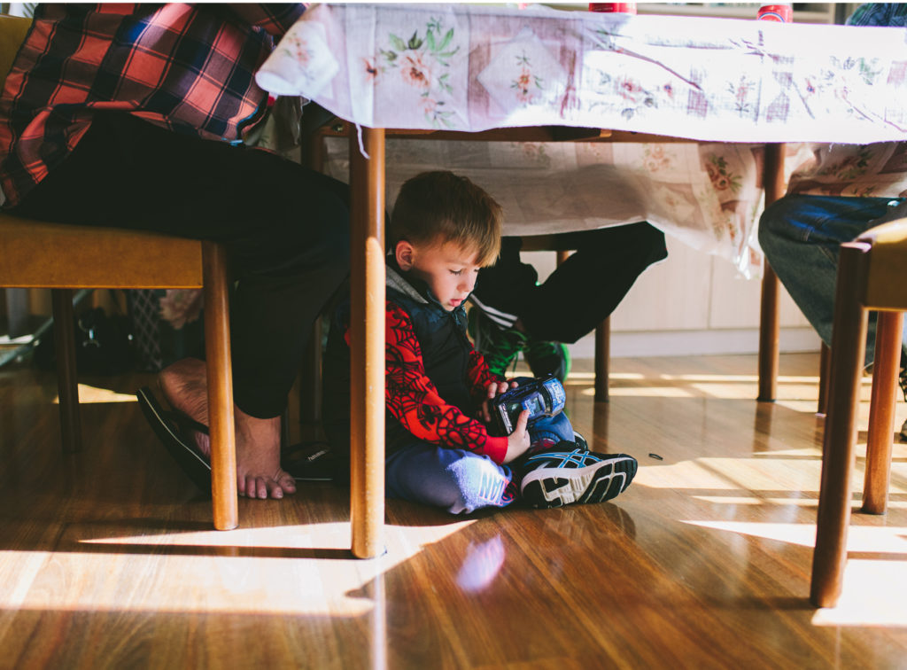 boy falls asleep under table